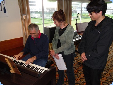 Claude Moffat trying out the Clavinova with Delyse Whorwood and her house guest from Mainland China, Ben, watching on.