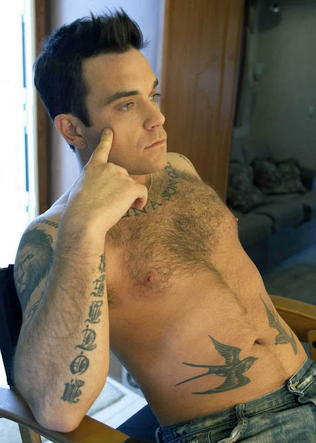 shirtless robbie williams reclining in a chair pensive showing off his hairy chest