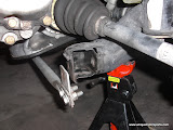 Unhook lower brace if you have one and front control arm bolt