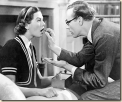 Henry Higgins puts marbles in Eliiza's mouth.