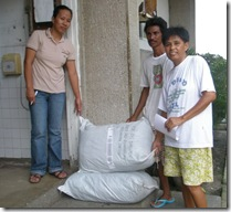 BFS Admin Asst. Ms Vivian Jatulan (leftmost) turns-over two sacks of goods to the representatives of the Pipindan Parish Mini Pastoral Council for distribution in their barangay