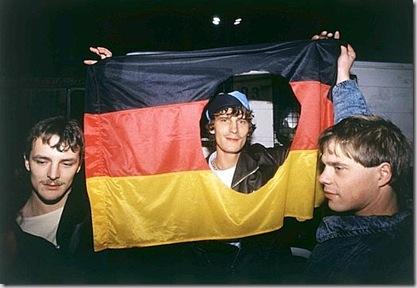 Wende, Giovani della Germania dell'Est festeggiano la caduta del Muro e del comunismo nella DDR, mostrando una bandiera tedesca da cui hanno ritagliato i simboli della DDR - © Wende - Ullstein Bild - Archivi Alinari