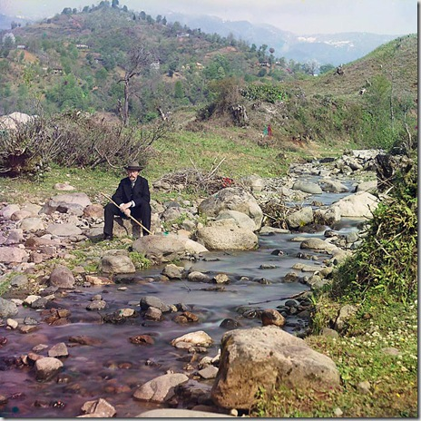 On the Karolitskhali River, self portrait of photographer Prokudin-Gorskii in suit and hat, seated on rock beside the Karolitskhali River, with mountains in background; between 1905 and 1915 Sergei Mikhailovich Prokudin-Gorskii Collection (Library of Congress).