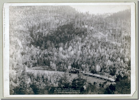 """Title: """"A pretty view."""" At """"picnic"""" grounds on Homestake Road Distant view of a train engine and several cars against a large wooded area. 1890. Repository: Library of Congress Prints and Photographs Division Washington, D.C. 20540"""