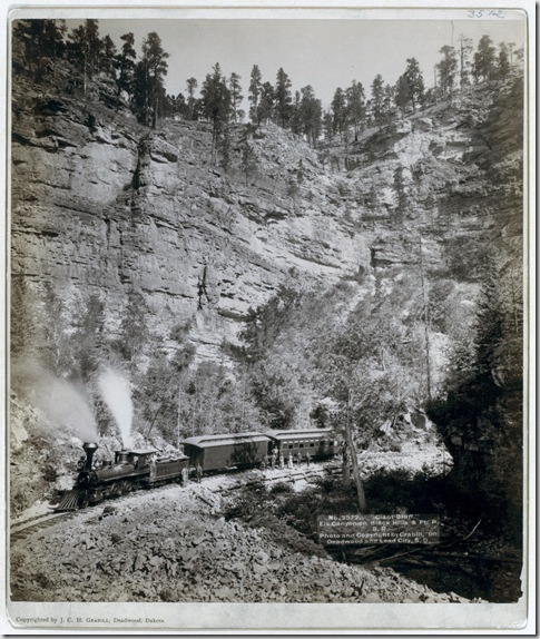 "Title: ""Giant Bluff."" Elk Canyon on Black Hills and Ft. P. R.R. A two-car train in front of a steep cliff; several passengers are posing in front of the train. 1890. Repository: Library of Congress Prints and Photographs Division Washington, D.C. 20540"