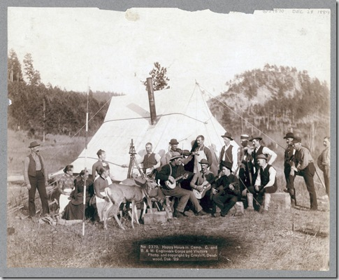 Title: Happy Hours in Camp. G. and B.&M. Engineers Corps and Visitors Small group of men and women and two deer in front of a tent. Some of the men are playing musical instruments. 1889. Repository: Library of Congress Prints and Photographs Division Washington, D.C. 20540