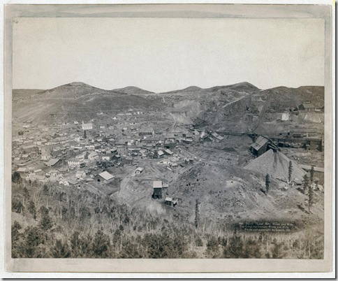 Title: Lead City Mines and Mills. The Great Homestake Mines and Mills Distant view of mining town; hills in background. 1889. Repository: Library of Congress Prints and Photographs Division Washington, D.C. 20540