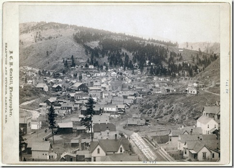Title: Deadwood, [S.D.] from Engleside Overview of homes and commercial buildings in small city; trees and mountains in background. 1888. Repository: Library of Congress Prints and Photographs Division Washington, D.C. 20540