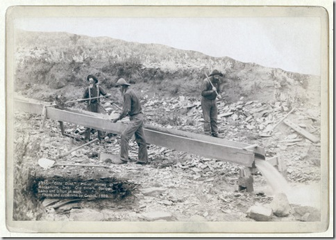 "Title: ""Gold Dust."" Placer mining at Rockerville, Dak. Old timers, Spriggs, Lamb and Dillon at work Three men placer mining with shovels, picks and pan. 1889. Repository: Library of Congress Prints and Photographs Division Washington, D.C. 20540"