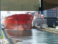 Os dois lado a lado, em direcções opostas. De notar o espaço livre de cada lado do navio vermelho. Ampliando a foto conseguem ver as locomotivas que ajudam o navio a manter o alinhamento durante a travessia do conjunto de comportas.