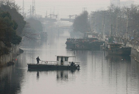 江苏无锡-2月8日:2005年2月8日,中国江苏无锡,一艘河道清污船在具有千年历史的古运河河道中清污。无锡古运河自禁停禁航后,环境有很大改善。Dennis Pu/China News Photo