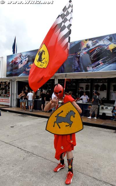болельщик Ferrari на фоне боксов Red Bull на Гран-при Венгрии 2010