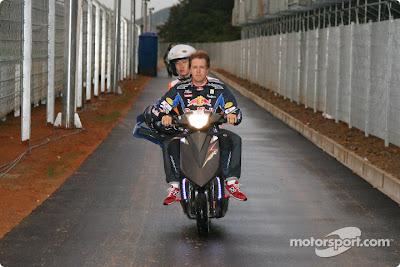 Себастьян Феттель возвращается на мопеде всемте с маршалом после схода с гонки Гран-при Кореи 2010