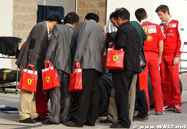 люди в пиджаках с пакетами Ferrari и Роб Смедли на Гран-при Кореи 2010