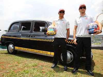 Льюис Хэмилтон и Дженсон Баттон на фоне такси на Гран-при Бразилии 2010