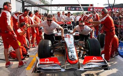 механики McLaren толкают болид Хэмилтона мимо механиков Ferrari