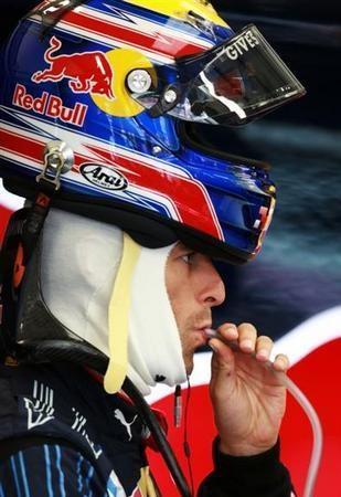 Марк Уэббер пьет со шлемом на голове на Гран-при Великобритании 2009