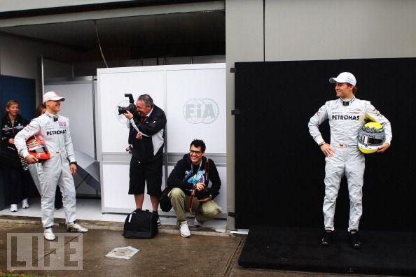 фотограф снимает Михаэля Шумахера в это время Нико Росберг стоит в сторонке на Гран-при Австралии 2011