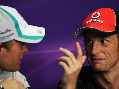 Нико Росберг что-то объясняет Дженсону Баттону на пресс-конференции пилотов в четверг на Гран-при Малайзии 2011