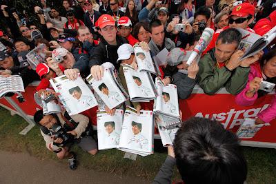 Камуи Кобаяши подписывает журналы со своим фото болельщикам Альберт-Парка на Гран-при Австралии 2011