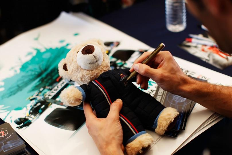 Марк Уэббер на автограф-сессии Гран-при Малайзии 2011 подписывает плюшевого мишку Red Bull