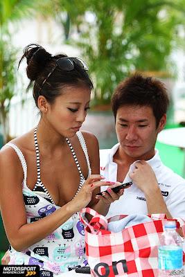 Камуи Кобаяши и Ю Абиру смотрят в телефон на Гран-при Малайзии 2011