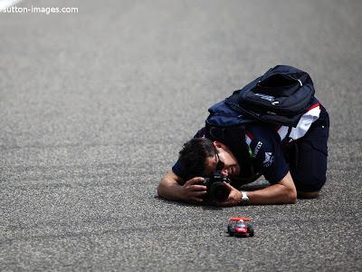 фотограф на Гран-при Китая 2011 снимает игрушечную машинку на настоящем гоночном треке