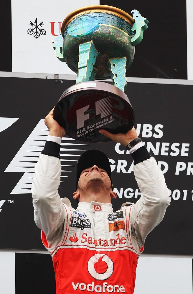 Льюис Хэмилтон наслаждается победным кубком на подиуме Гран-при Китая 2011