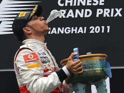 Льюис Хэмилтон пускает струю шампанского в Шанхайски трофей на подиуме после победы на Гран-при Китая 2011