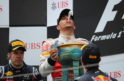 Льюис Хэмилтон пускает струю шампанского в Шанхайски трофей в окружении Себастьяна Феттеля и Марка Уэббера на Гран-при Китая 2011