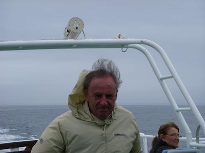 海風に吹かれるデッキの乗客