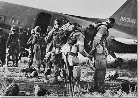 PARATROOPERS, IDENTIFIED BY WHITE ARM BANDS, preparing to emplane for Sicily.