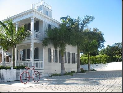 Rød sykkel med hvitt hus