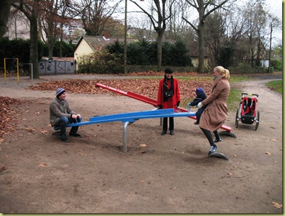M L and parents on the blue seesaw