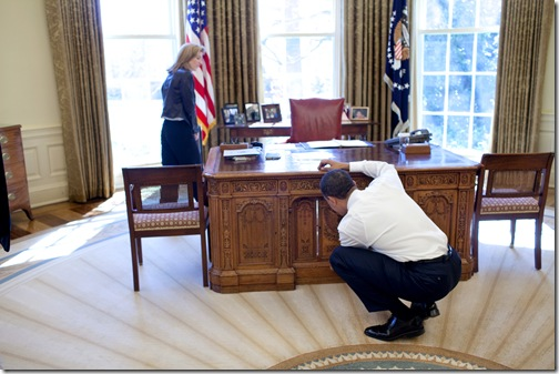 President Barack Obama examines  the Resolute Desk on March 3, 2009, while visiting with Caroline Kennedy Schlossberg in the Oval Office. In a famous photograph, her brother John F. Kennedy Jr., peeked through the FDR panel, while his father President Kennedy worked. <br />Official White House Photo by Pete Souza