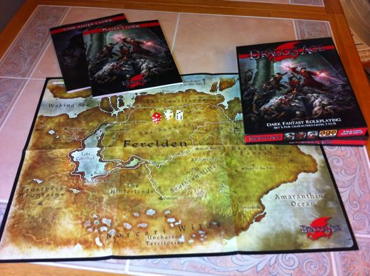 [Image: The Dragon Age kit, spread out across my table. Consists of two books, a map, and three dice (two white, one red).]