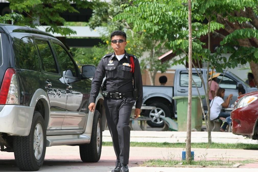 Полицейский в форме рядом с Isuzu Mu7