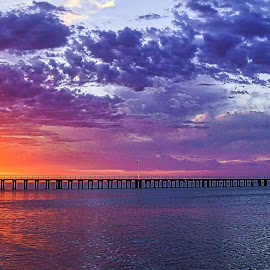 Sunset near the Pier by Keith Walmsley - Landscapes Sunsets & Sunrises ( clouds, water, orange, red, blue, pier, yellow, beach, landscape, natural )