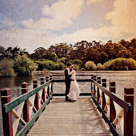 Love at Jetty's End by Alan Evans - Wedding Bride & Groom ( clouds, hills, daylesford, wedding photography, waterscape, aj photography, lake, jetty, landscape, daylesford wedding photographer, mountains, blue sky, wedding, pier, bride and groom, bride groom )