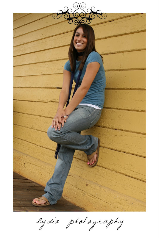 Senior girl with her foot against a yellow building at Simpson senior lifestyle Empire Mine portraits in Colfax, California
