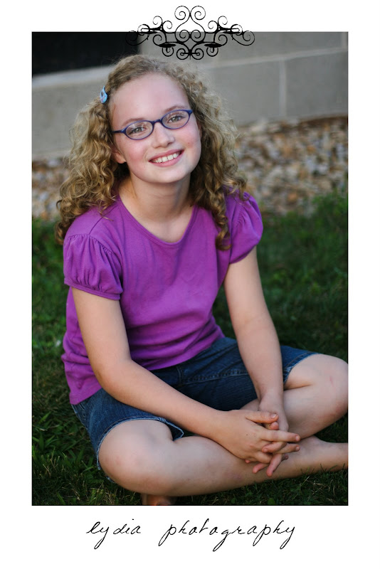Little girl with curly hair and glasses at lifestyle kids portraits on a farm in Indiana, Pennsylvania