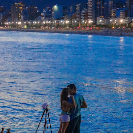 At Ipanema beach by Tomek Karasek - People Couples ( water, ipanema, kissing, hugging, sea, couple, night, evening, light, city )