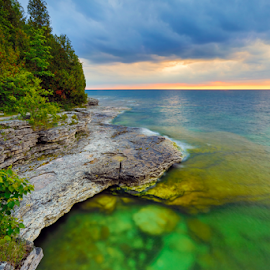 Cave Point Dawn by Kenneth Keifer - Landscapes Waterscapes ( stormy, stone, rock, shine, storm, sunshine, light, boulders, midwest, cliff, forest, sunlight, door peninsula, dawn, rising, turquoise, trees, aqua, cave point, early, peninsula, shore, wisconsin, colorful, door county, rocky, shining, aquamarine, landscape, coastline, coast, sun, dawning, dramatic, shoreline, long exposure, rugged, clouds, water, jacksonport, green, scenic, seascape, great lakes, storm clouds, daybreak, morning, woods, lake michigan, splashing, color, sunrise )