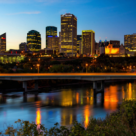 by Joseph Law - City,  Street & Park  Skylines ( blue sky, lighting, bushes, city of edmonton, buildings, reflections, in the evening, river )
