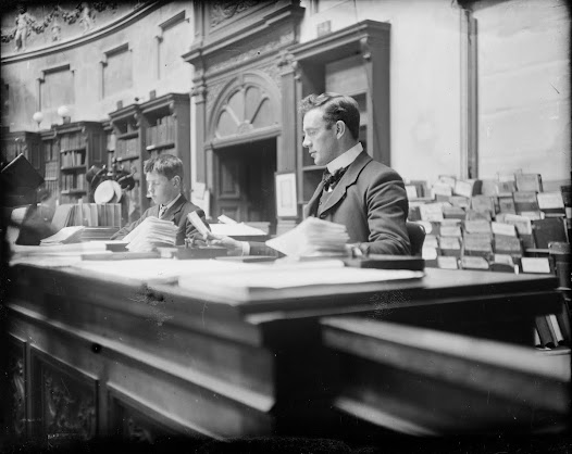 Library assistant and boy attendant in the Reading Room of the National Library