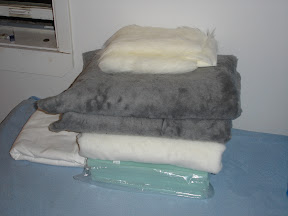 A pile of grey and white faux fur on a bed...