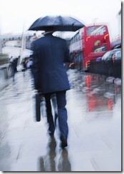 Motion blur image of wet business man with briefcase and umbrella walking to work through the London rain