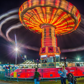 Swings by Jon Cody - City,  Street & Park  Amusement Parks ( ride, spinning, carnival, swings, fair, the mood factory, mood, lighting, sassy, pink, colored, colorful, scenic, artificial, lights, scents, senses, hot pink, confident, fun, mood factory  )