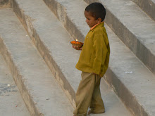 A young boy celebrates Diwali by setting little flaming cups into the Ganges at the ghat by the bridge.