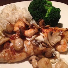 Broiled Redfish with a modified Melissa topping of Scallops, Shrimp, Mushrooms and Lump Crabmeat. A